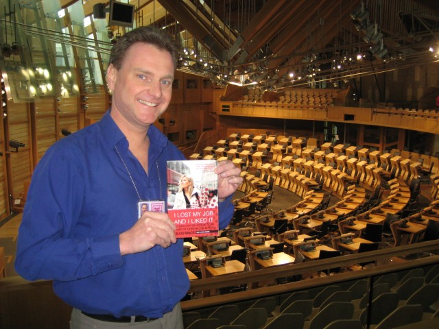 "Myself in the Debating Chamber of the Scottish Parliament with a copy of the book I helped Lilou Mace write: ""I Lost My Job and I Liked It"". (Photo courtesy of Stefan Buettner)"