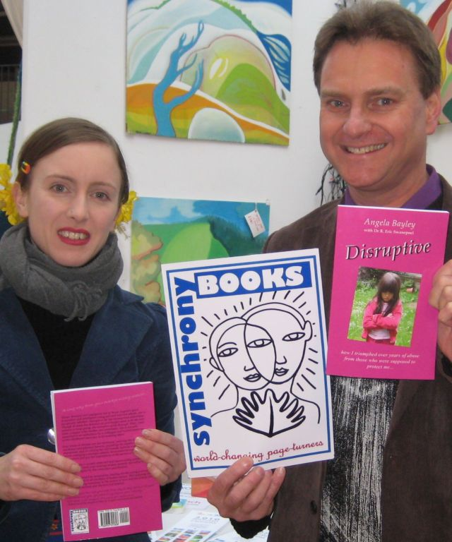 Clare Galloway and Eric Swanepoel display the Synchrony Books logo, designed by Clare, and copies of 'Disruptive', the cover of which was designed by Vroni Holzmann. Picture taken in front of Clare's stall in the out of the Blue Drill Hall Art Market on 12 December 2009 by a kind stranger.